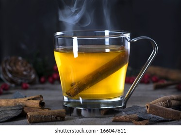 Hot  whiskey, rum, apple or brandy toddy cocktail drink with cinnamon set on rustic wood