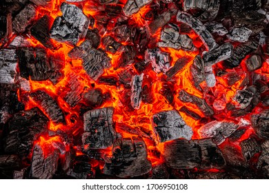 Hot white and black coals smolder in the grill