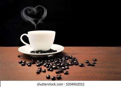 Hot White Coffee cup and Coffee beans on the wooden table and black background.Copy space blank for text.Heart steam sign for Valentine's Day.Coffee Lover.