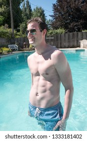 Hot white guy with no shirt and sexy body standing next to an outdoor swimming pool in the summer sun in aviator sunglasses looking cool and confident. Man with great body posing next to swimming pool