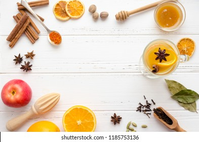 Hot white mulled wine in glass with orange, cinnamon sticks and star anise with spices and ingredients on white wooden background. Spicy warm beverage. Seasonal mulled drink. Copy space. Top view.