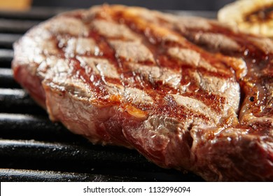 Hot Whole Grilled Ribeye Beef Steak on Black Barbecue Grill Background. Fresh Well Done Beefsteak.