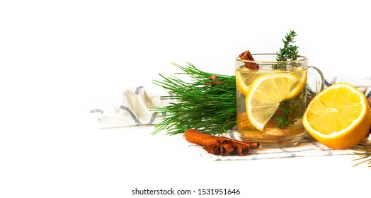 Hot winter aromatic drink. Ginger tea with lemon, cinnamon, star anise, cones and green Christmas tree branches on a white background, copy space.