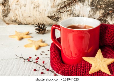 Hot winter tea in a red mug with star shaped christmas cookies and warm scarf - rural still life