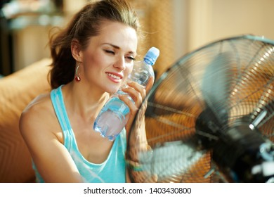 hot woman with bottle of cold water using electric metallic fan at modern home in sunny hot summer day.