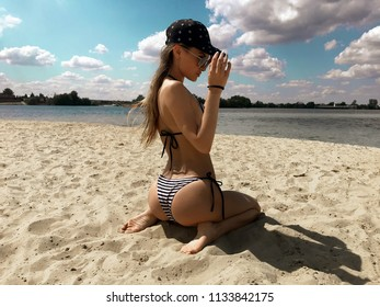 Hot young lady in stripes swimsuit looking away in sunglasses at the beach summer time