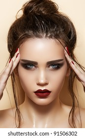 Hot young woman model with sexy dark red lips makeup, strong eyebrows, clean shiny skin and wet bun hairstyle. Beautiful fashion portrait of glamour female face