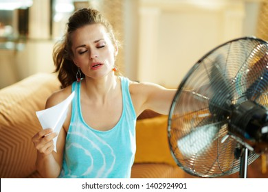 hot young woman in the modern house in sunny hot summer day in the front of working fan suffering from summer heat.