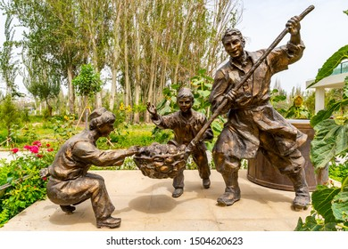 HOTAN, CHINA - JULY, 2019: Picturesque Kunlun Lake Park View of a Uyghur Father and Two Sons Cooking Food Statue on a Cloudy Blue Sky Day