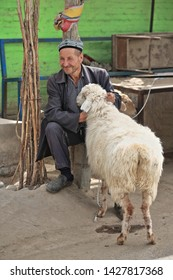Hotan, China-October 4, 2017: Uyghurs are a Turkic people living mainly in the Xinjiang Uyghur Autonomous region. Smiling livestock handler sitting at the Livestock Market with his fat-tailed sheep.