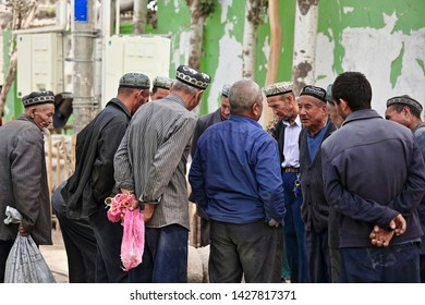 Hotan, China-October 4, 2017: Uyghurs are a Turkic people living mainly in the Xinjiang Uyghur Autonomous reg. Group of livestock handlers discuss the fat-tail sheep business at the Livestock Market.