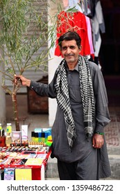 Hotan, Xinjiang, China-October 3, 2017: Pakistani middle-aged man in shalwar kameez attire, salesman in the city's bazaar, serves his perfumery stall while posing for tourists visiting the market.