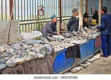 Hotan, Xinjiang, China-October 4, 2017: Uyghur vendors sell jade stones and other minerals at their market stalls in the Jade Bazaar by the Yurungkax river-bargaining with customers hunting for sales.