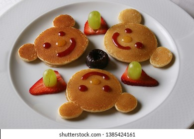 Hotcakes for children with a bear shape accompanied by strawberries, grapes, and marmalade