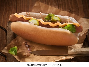 Hotdog bun with sausage with mustard and pickles