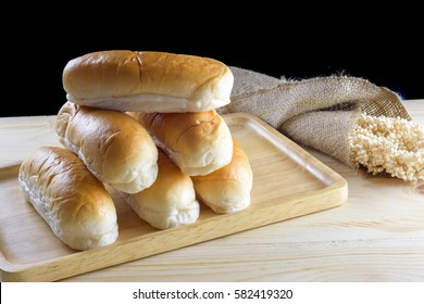 Hotdog buns in wood plate on wooden table, isolated on black