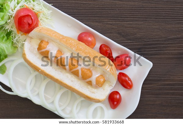 Hotdog with dressing mustard and vegetables in white dish on dark table / Selective focus and space for text and top view image