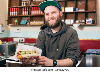 Hotdog - friendly salesman and customer in a fast food snack bar