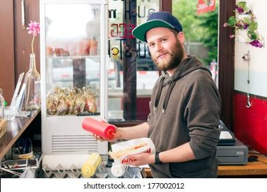 Hotdog - friendly salesman and fresh ingredients in a fast food snack bar