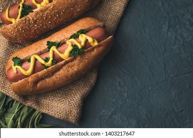 hotdog and sausage with sage vegetables on old background