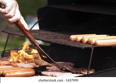Hotdogs and hamburgers on the grill at a summer cookout.