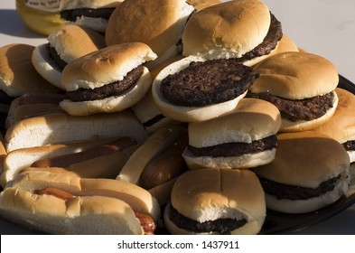 Hotdogs and hamburgers piled up at a summer cookout.