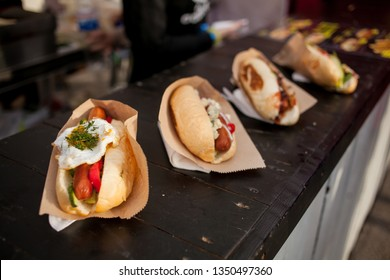 Hotdogs lie in a row. street food. many hotdogs. Plate of freshly grilled hotdogs with mustard. Tasty and delicious hamburger. Once branded as an American junk food and fast food