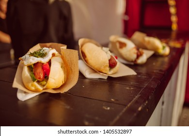 Hotdogs lie in a row. street food. many hotdogs. Plate of freshly grilled hotdogs with mustard. Tasty hamburger. Once branded as an American junk food and fast food. Vintage photo processing