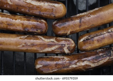 Hotdogs on a grill.