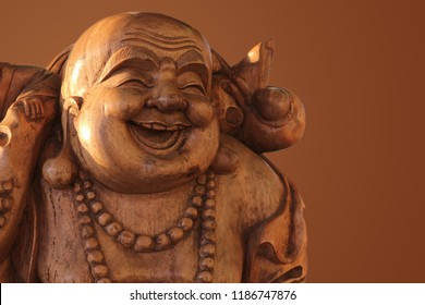 Hotei or the laughing Buddha is a wooden statue on a brown background..