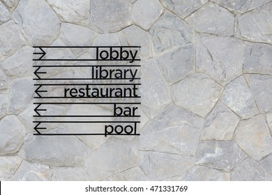 Hotel arrow signage on stone wall background. Lobby, Library, restaurant, bar and pool sign.