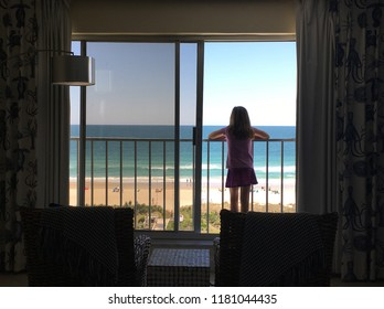 At a hotel balcony, a young girl looks out over the beach
