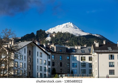 A hotel with the Bansko Ski Resort on the Pirin Mountains at the background in Bansko, Bulgaria.