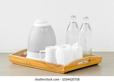 Hotel basic accommodation provide kettle set for self service. Include, kettle, glass of bottle, coffee cup, glass of water orderly in the wooden tray.