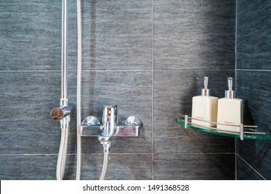 Hotel bathroom closeup with stainless hanging shower, bottles of shower and shampoo gel