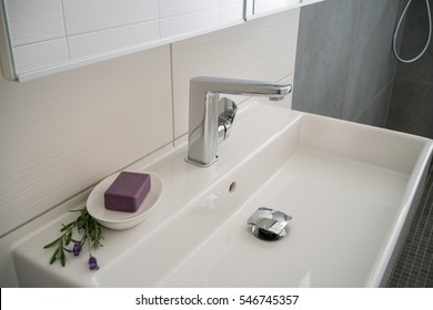 Hotel bathroom with herbal soap and purple flowers displayed on the modern white rectangular hand basin