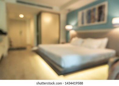 Hotel bedroom blur background guest room interior with blurry comfortable king size bed white bedsheet, work table desk and chair furniture