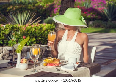 Hotel breakfast woman relaxing drinking fresh juice. Happy tourist enjoying healthy food. Sun outdoors.