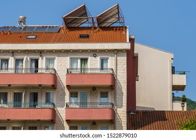 Hotel building, windows, balconies and solar panels on the roof, fragment.