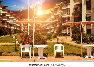 Hotel buildings and green park with grass, bushes, flowers, white plastic chairs and table with forest and sky with sunset on a background