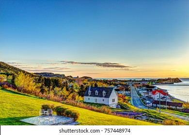 Hotel chairs on hill during sunrise in Perce, Gaspe Peninsula, Quebec, Canada, Gaspesie region with cityscape