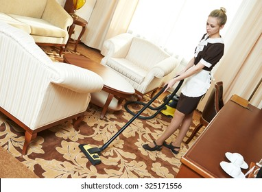 Hotel cleaning service. female housekeeping worker with vacuum cleaner in room apartment