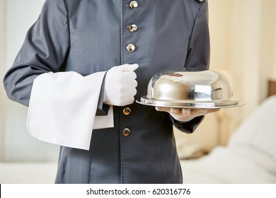Hotel clerk serving food with cloche in a hotel room