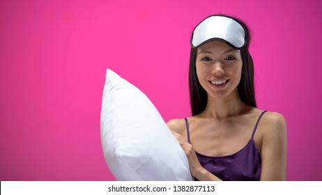 Hotel client holding pillow and looking at camera, comfortable bed, HoReCa