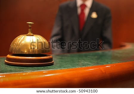 Hotel Concierge: bell on the reception front desk with waiter