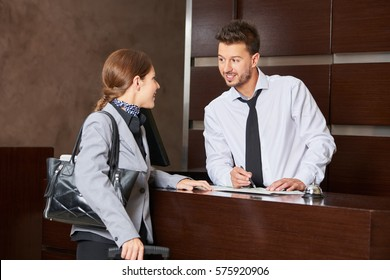 Hotel concierge offering tipps on city map to female guest