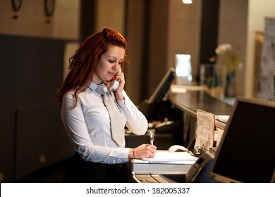 Hotel Concierge .Reception of hotel, desk clerk, woman taking a call and smiling.