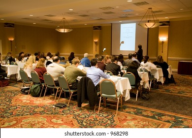Hotel conference room full of people participating in the business training.