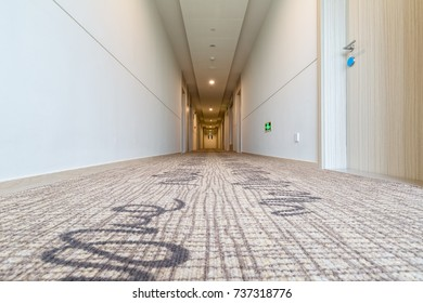 hotel corridor with carpet, low angle view