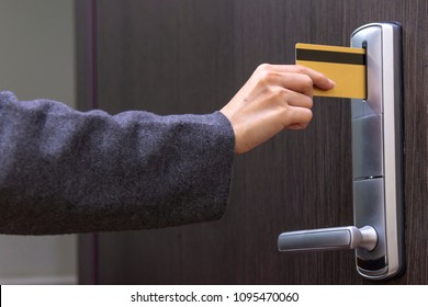Hotel door - woman's hand inserting a magnetic stripe hotel key card in front of the electronic card key door lock